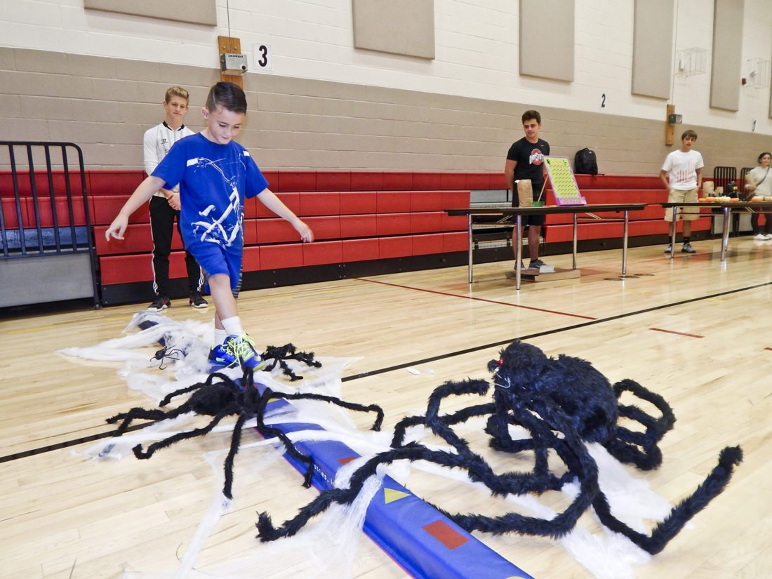 Tribune Chronicle / Bob Coupland Milo Moss, 6, of Girard, a student at Prospect Elementary School in Girard, steps carefully across a short beam to avoid spiders and cobwebs. It was one of the Halloween-themed activities at the school's annual Harvest Fest. The event was for students at Girard Prospect Elementary and Girard Intermediate schools.