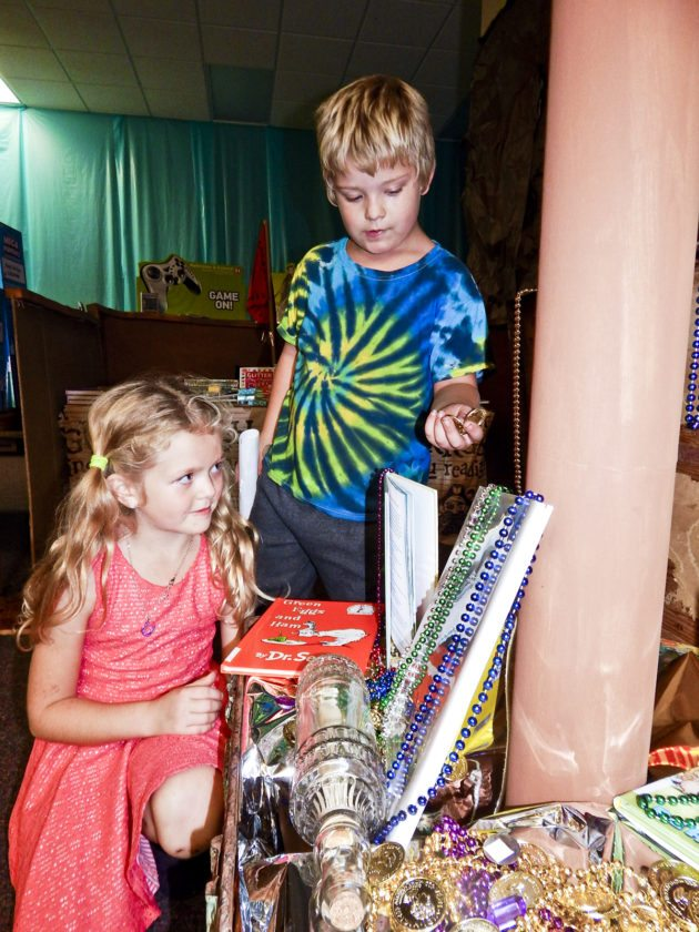 Bascom Elementary School second-graders Lillian Simmons, 7, and Jack Gut, 7, look for items in a treasure chest at the school's Bookaneer Book Fair, which has a pirate theme.