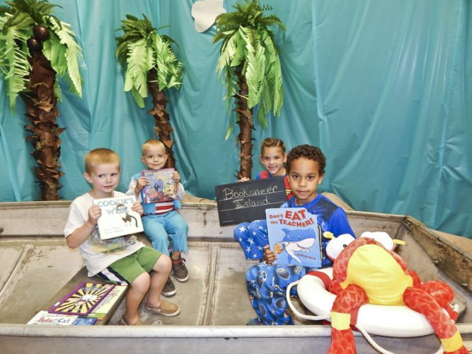 Small boats and a treasure chest decorate the Bascom library for the school book fair. In a boat are, from left, preschoolers Corbin Simmons, 5, and Max Gut, 4, and second-grader Riley Rowe, 7, and first-grader Giles Davis, 6.