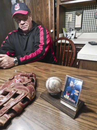 Jim Campbell of Howland sits at his Willow Drive kitchen table with the glove and ball that was launched by Tribe slugger on July 16, 1995, to win a crucial game against the Oakland A's that helped propel them to a 100-win season and an eventual World Series berth.