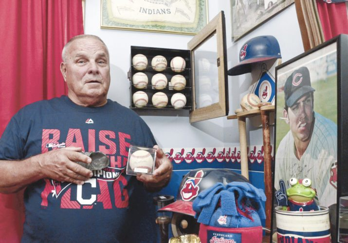 102516...R INDIANS FAN 1...Leavittsburg...10-25-16... Cleveland Indians fan Ronald Clark of Leavittsburg holds an autographed baseball from Ray Boone, a member of the 1948 Indians World Series team, with a shadow box of autographed baseballs from the 1948 Indians team hanging on the wall over his shoulder...Clark is holding a silver Cleveland Indians ashtray in his right hand...by R