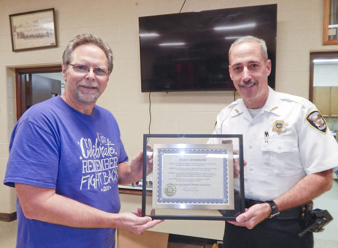 Tribune Chronicle  / Bob Coupland  Paul Chaney with the Lordstown Neighborhood Crimewatch, left, recently presented a plaque to Lordstown Police Chief Brent Milhoan as residents thanked local police officers and firefighters for their service to the community.