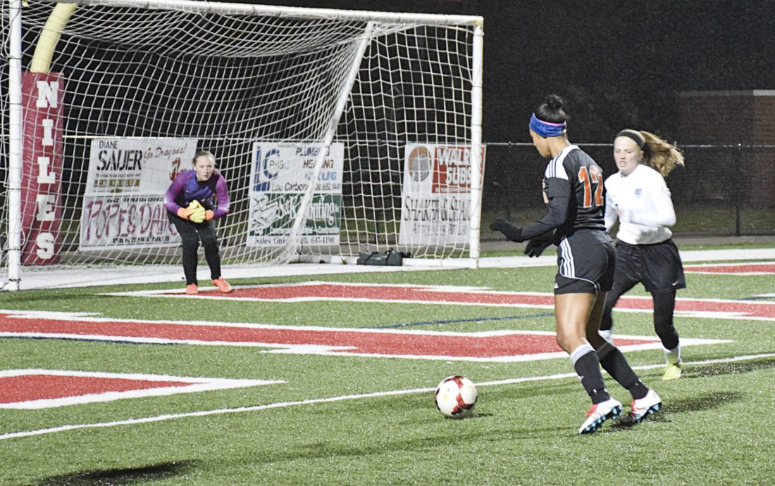 Tribune Chronicle / Joe Simon Howland's Amarah Howard (12) lines up a shot while Lakeview goalkeeper Miranda Meffe, left, prepares to make a save during a Division II district final Thursday. Howland won, 3-0.
