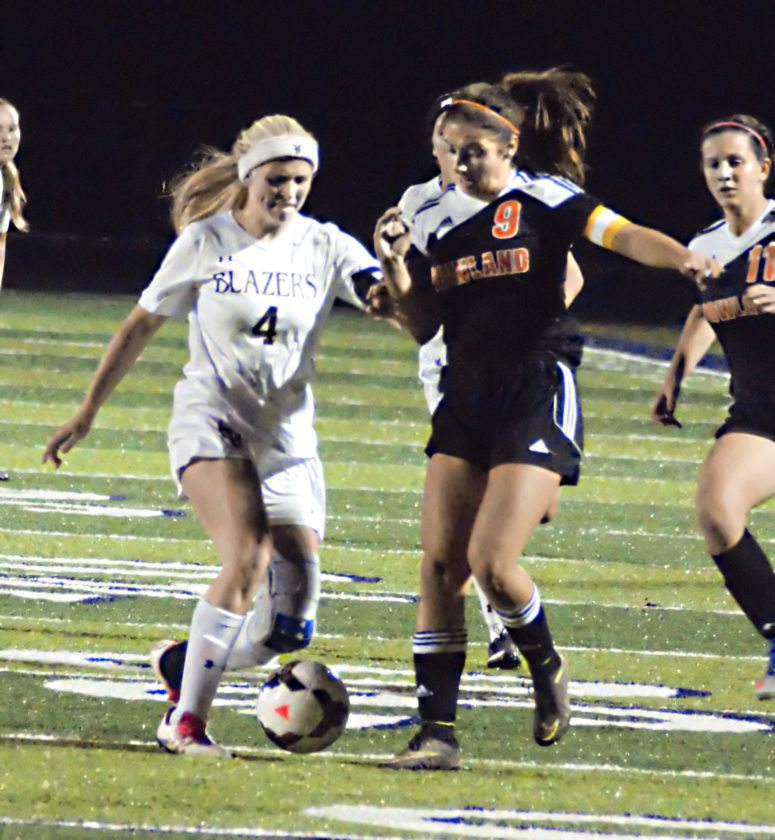 Tribune Chronicle / Bob Ettinger Chloe Richards of Hathaway Brown, left, tries to take the ball from Sara Ciletti of Howland, right, in Division II regional soccer action at Twinsburg on Tuesday night.