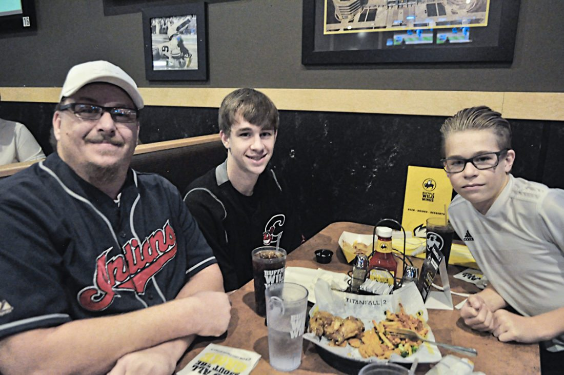 Tribune Chronicle / Renee Fox John Harsany, Jacob Harsany, 17, and Austin Harsany, 13, all of Warren, started Wednesday night with an early optimism at Buffalo Wild Wings in Niles. Jacob Harsany said the Cleveland Indians are an inspiration to him, a player himself, and that maybe he should have worn the lucky socks he wears for his own games.