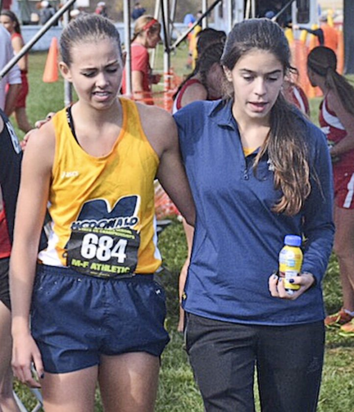 McDonald's Malina Mitchell, left, is helped off the course by teammate and friend Ally Jamison. Mitchell, who was running after breaking her foot Saturday at the Division 3 girls state cross country meet in Hebron. The Blue Devils took fifth.