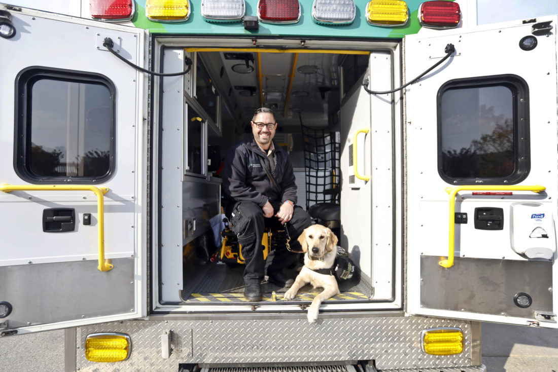 In this Nov, 2, 2016 photo, U.S. Army veteran Louis Belluomini and his service dog, Star, sit in an ambulance at ProMedica Flower Hospital in Sylvania, Ohio. Belluomini, a ProMedica Air and Mobile medic, served with the U.S. Army, first with a combat military police unit in Iraq, then a few years later in Afghanistan. He was diagnosed with PTSD in 2009. (Amy E. Voigt/The Blade via AP)