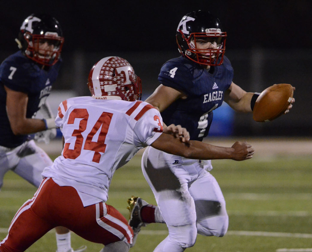 110516...R TORONTO@JFK 4...Warren...11-05-16... JFK's QB #4 Gregory Valent fights off Toronto's #34 Max Tice while rushing for yardage as JFK's #7 Evan Boyd follows the play during 1st Qt. action...by R. Michael Semple