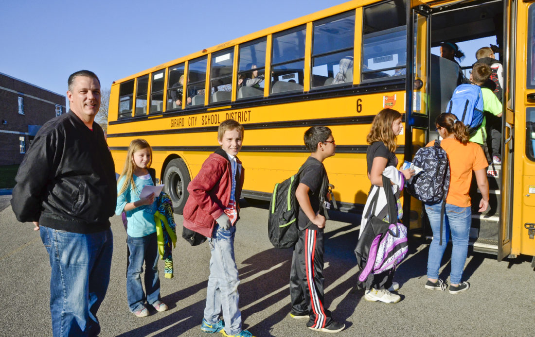Tribune Chronicle / R. Michael Semple  Girard Intermediate School Principal Gregory Bonamase accompanies students as they get onto their bus at the end of the school day Friday. The school was one of three Trumbull County schools to receive the Momentum Award from the Ohio Department of Education.