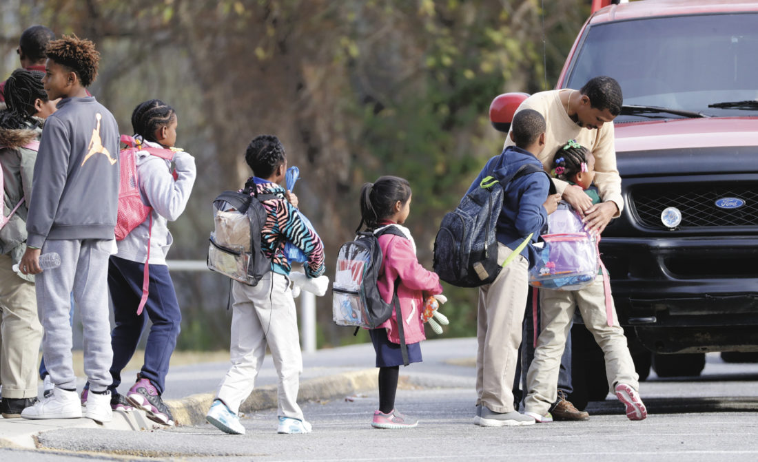 A child gets a goodbye hug as students are picked up from Woodmore Elementary School Tuesday, Nov. 22, 2016, in Chattanooga, Tenn. A school bus driven by Johnthony Walker, 24, crashed while transporting children home from the school Monday, killing at least five students. Walker has been arrested on charges including vehicular homicide, reckless driving and reckless endangerment. (AP Photo/Mark Humphrey)