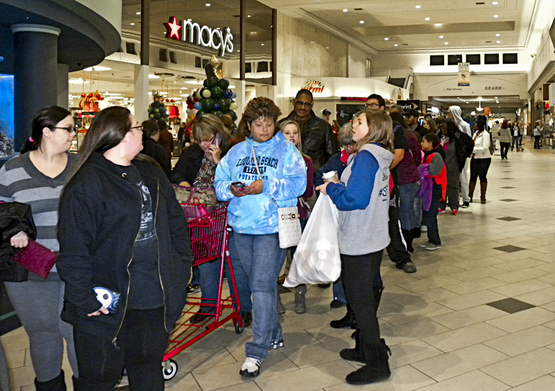 "Tribune Chronicle / Emily Earnhart  Shoppers waited in a line as long as the mall's main corridor Thursday evening to pick up a giveaway bag of coupons and prizes at the Eastwood Mall's ""Rock the Mall"" event."