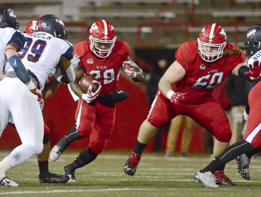 YSU's #29 Martin Ruiz follows the blocking of teammate #60 Gavin Wiggins as Samford's #99 Ahmad Gooden goes for the tackle during 2nd Qt. action...by R. Michael Semple