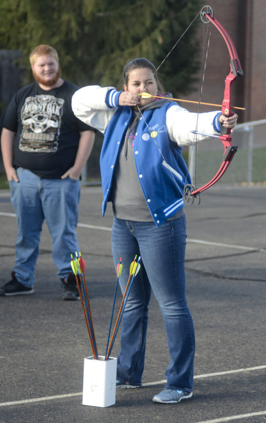 Tribune Chronicle / R. Michael Semple  Maplewood High School senior Megan McClosey, 18, of Mecca, learns archery skills during the school's outdoor appreciation class as classmate Jarrett Mitchell, 17, watches. The class, which teaches students skills like archery, fishing, gun safety and boating safety, is taught by Terry Muresan.
