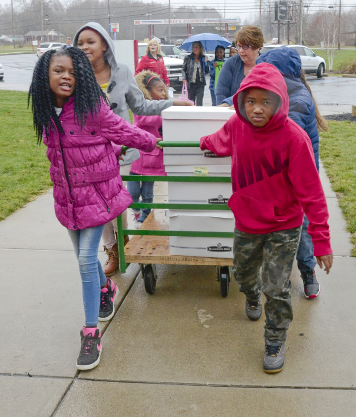 113016...R JEFF BOOKS 2...Warren...11-30-16... MaKayla Bee, 10, left, and Kenyan Patterson, 9, both 4th graders at Jefferson PK-8 school along with other 4th grade students, roll the donated books (200 new and 50 slightly used) into the school and onto the library Wednesday morning...by R. Michael Semple