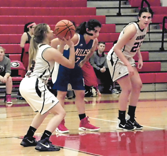 Tribune Chronicle / Eric Murray Girard's Samantha Cave, left, shoots a free throw while teammate Saralynn Essad, right, and Niles' Dakota Naples, middle, prepare to rebound during their game Wednesday. Girard won, 50-39.