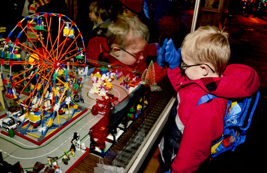 120216...R WARREN X-MAS 1...Warren...12-02-16... With thoughts of Christmas in the air Logan Schaaf, 5, of Warren, views the colorful display of Legos in the front window of Trumbull Art Gallery (TAG) along N. Park Ave. while attending Christmas in the Square Friday evening...by R. Michael Semple