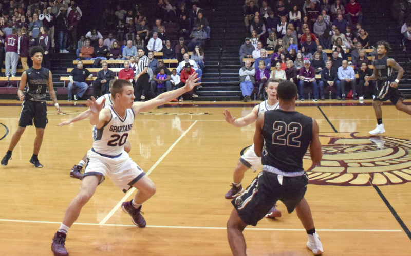 Tribune Chronicle / John Vargo Boardman's Mike Melewski (4) and Coleman Stauffer (20) guard Warren G. Harding's Lynn Williams during Friday's 52-51 Boardman home victory over the Raiders in the opener for both teams.