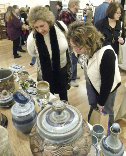 Tribune Chronicle/Andy Gray Judy Babik, left, who teaches visual art at Lincoln PK-8 School in Warren, and her sister, Nancy Kropolinsky of Austintown, look at stoneware from Winegar Pottery at the 46th Art & Artisan Show at the Butler Institute of American Art in Youngstown.