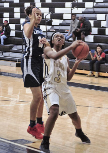 Tribune Chronicle / Bob Ettinger Kia Allen of Warren G. Harding prepares to go up strong to the hoop after getting by Aja Custer of Max S. Hayes in non-conference action on Saturday afternoon at Harding.