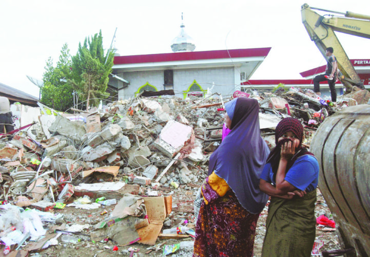 Acehnese women survey the damage after an earthquake in Ulhee Glee, Aceh province, Indonesia, Thursday, Dec. 8, 2016. Thousands of people in the Indonesian province of Aceh took refuge for the night in mosques and temporary shelters after a strong earthquake Wednesday killed a large number of people and destroyed dozens of buildings. (AP Photo/Binsar Bakkara)