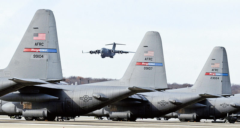 112513...R AIRLIFT AID 2...Vienna...11-25-13... An Air Force C-17 prepares to land at the Youngstown Air base Monday morning (C-130's in foreground) while on a humanitarian airlift...The Air Force C-17 was loaded with 14 pallets of humanitarian cargo for transport to Guatemala as part of the Mission for Love program...by R. Michael Semple