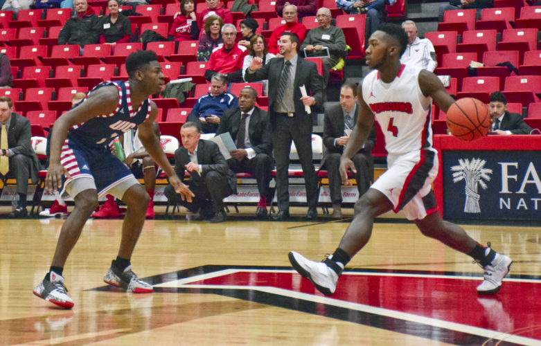 Tribune Chronicle / John Vargo YSU's Jeremiah Ferguson, right, passes the ball to a teammate while being guarded by Michael Kolawole of Illinois-Chicago Saturday night at Beeghly Center in Youngstown. The Penguins dropped a 92-89 overtime decision to the Flames.