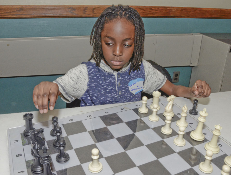"011617..R MLK@YWCA 1,,,Warren...01-16-17... Josiah Johnson, 7, of Warren , a member of ""Chess Is Life"" organization practices his chess skills while attending the MLK forum at the Warren YWCA Monday afternoon...by R. Michael Semple"