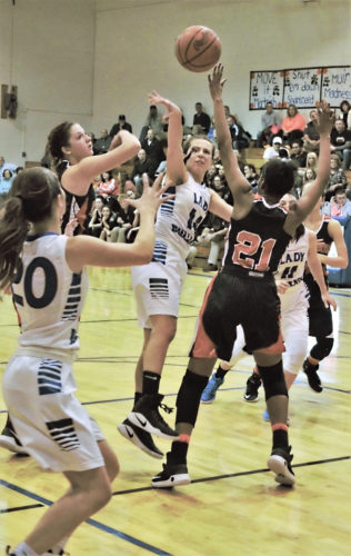 Tribune Chronicle / Bob Ettinger Cammie Becker of Lakeview drops a pass down to Lindsay Carnahan on the baseline as Samarra Caffey (21) and Sara Price of Howland defend Wednesday night in Cortland.
