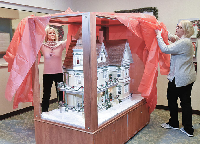 In this Dec. 20, 2016 photo, Child Life volunteers Janice Selden, left, and Susanne  Frey unveil a fully restored and outfitted dollhouse at the Alexian Brothers Women's and Children's Hospital in Hoffman Estates, Ill. The donated 13-room, three-story Victorian dollhouse is an inspiration for recovering children at the hospital. (Bob Chwedyk/Daily Herald, via AP)