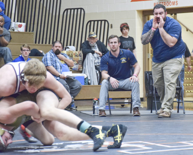 Tribune Chronicle / Joe Simon First-year Brookfield coach Ben Solomon, right, yells instructions to wrestler Tyler Lucas, foreground, while assistant coach Tyler Thompson, middle, looks on Saturday at the Howland Invitational.