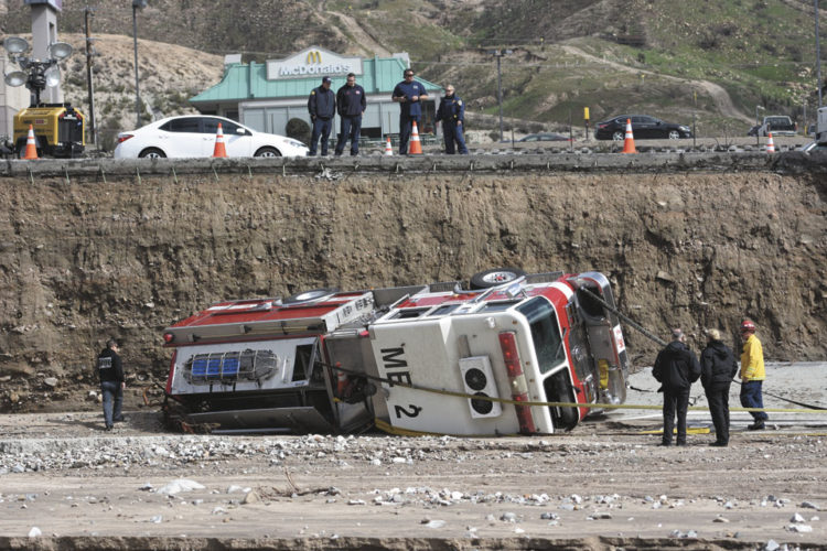 Officials look over the scene where a San Bernardino County Fire Department fire engine fell Friday from southbound Interstate 15 where part of the freeway collapsed due to heavy rain in the Cajon Pass, Calif., Saturday, Feb. 18, 2017.    A huge Pacific storm that parked itself over Southern California and unloaded, ravaging roads, opening sinkholes  eased off Saturday but it was only a temporary reprieve as new storms took aim farther north. (David Pardo/The Daily Press via AP)