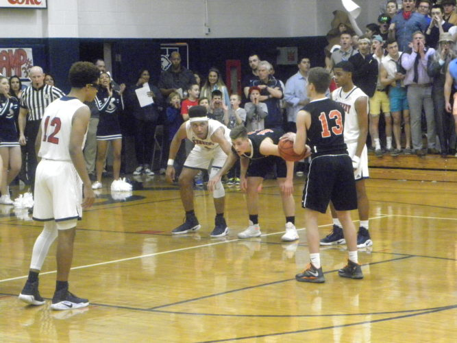 Tribune Chronicle / Eric Murray Howland's Connor Tamarkin shoots free throws as teammate Mike Massucci and JFK's Antonio McQueen, center, wait for Tamarkin to shoot, along with JFK's B.J. Williams.