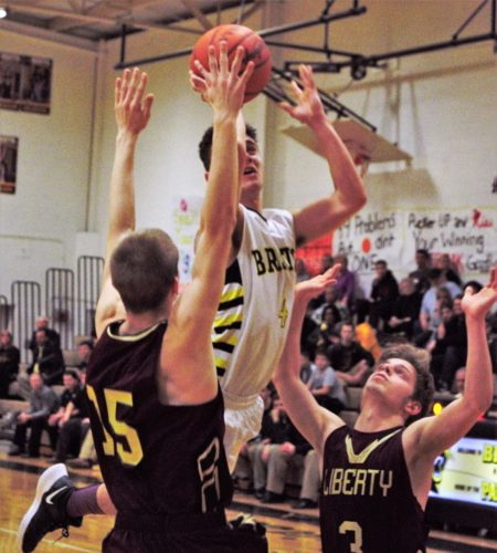 Tribune Chronicle / Bob Ettinger Tommy Donadio of Bristol drives to the rim as Travis Myers (15) and Kevin Hawn (right) of Liberty defend at Bristol on Tuesday night.