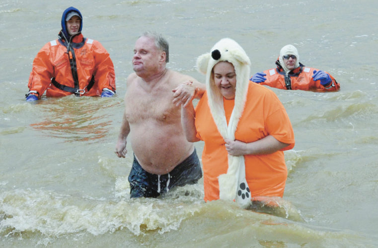 "Tribune Chronicle  / R. Michael Semple The American Cancer Society held its annual ""Brrr for a Cure"" polar bear plunge Saturday at Lake Milton. Beanie Bump, 63, of Mecca, left, a 33-year cancer survivor who is blind, takes the plunge with help from his niece, Kerri DeBolt of Mecca, right. Bump and DeBolt are on the Kmart United Auto Workers Local 1112 team."