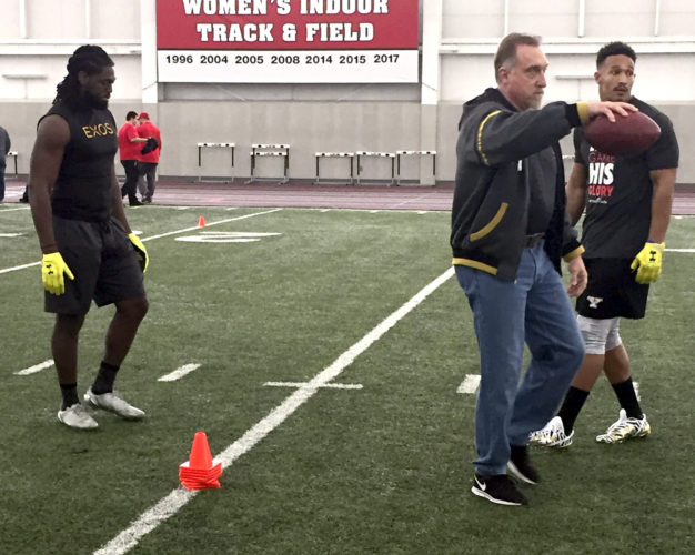 Tribune Chronicle / Joe Simon Former NFL linebacker and current New York Jets scout Kevin Greene, middle, instructs Youngstown State defensive lineman Derek Rivers, right, and Avery Moss during YSU's Pro Day on Tuesday.