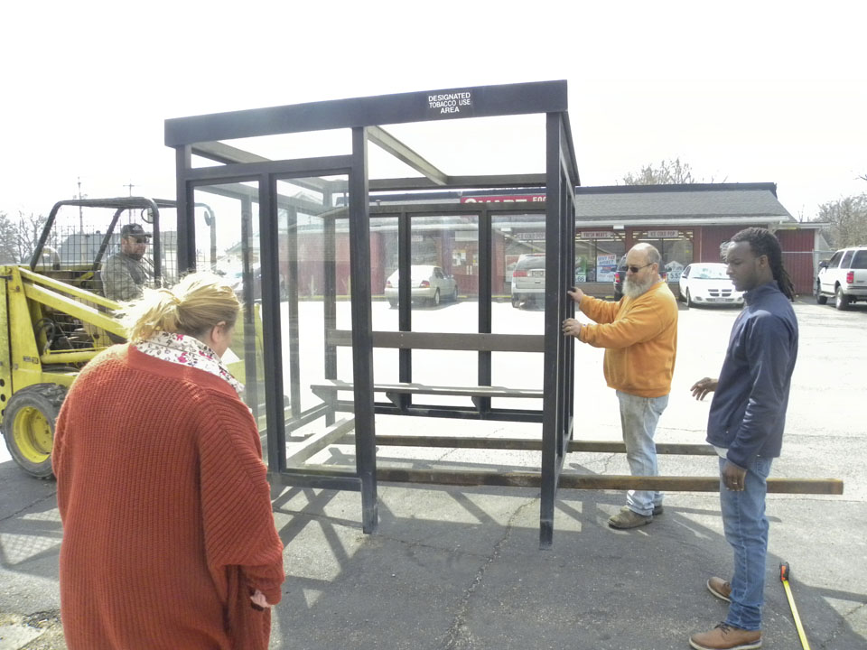 J.R. Bacorn, of Warren, far left, drives a forklift while Michella Comanescu, of the Economic Justice Team, center left, Jack Bacorn, of Warren, center right, and Miles Jay, also of the Economic Justice Team, far right, help guide the bus shelter to the proper location in front of the Smart Food Store on US Route 422. Volunteers with the Trumbull Neighborhood Partnership placed two bus shelters throughout Warren on Tuesday to give residents places to safely wait for transportation.