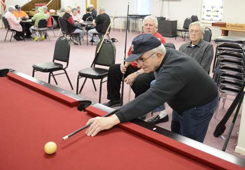 Joe Silva takes a shot during a game of pool on Feb. 2, 2017 at the Selinsgrove Senior Center in Selnsgrove, Pa.  The number of seniors like Maurer who are aging alone without a spouse or close family nearby is on the rise, senior advocates say.  (Robert Inglis/The Daily Item via AP)
