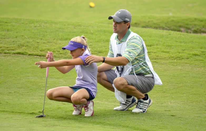 Special to Tribune Chronicle  Gianna Clemente, 8, left, is lining up a putt with the assistant of her caddie and father, Patrick.