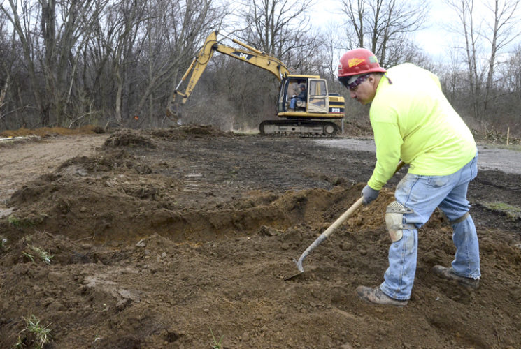 032717...R TRAIL 1...Howland...03-27-17...Laborer Chuck Bulick, right, grades dirt as Frank Rappich operates an excavator in the background as construction continues on the Trumbull County MetroParks North Road Nature Preserve Trailhead parking lot Monday morning...Both work for Foust Construction of Girard...by R. Michael Semple