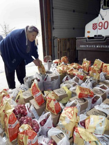 Deborah Hall, a volunteer, sorts food items for the Salvation Army produce giveaway,