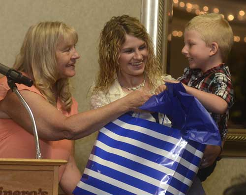 """Michael Bingham, 4, right, is eager to see what is in the gift bag presented to his paternal grandmother Cynthia Bingham, left,  while being held by his paternal aunt Courtney Bingham, center, during the Trumbull County Children Services """"Rising Up and Moving On"""" Community luncheon...by R. Michael Semple"""