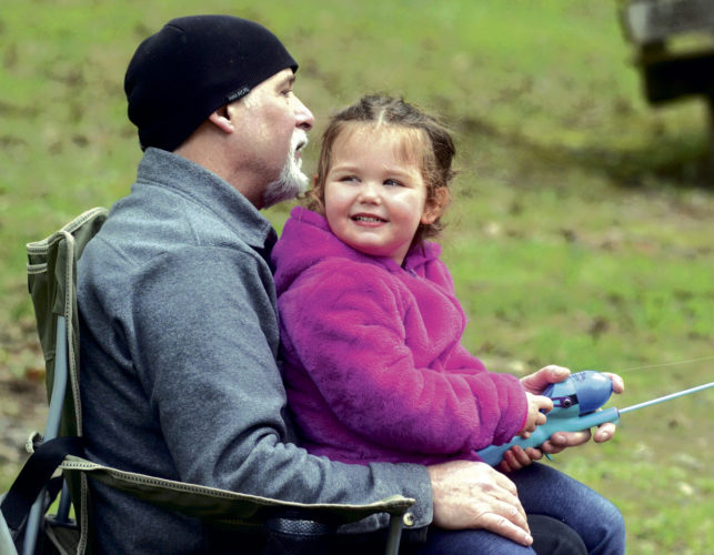 042217...R FISHING 1...Mecca...04-22-17...Trumbull County Rod and Gun Club,,,Grandfather Bob Brode of Austintown watches the fishig line as granddaughter Lilliana Heeter, 3, of Austintown, looks elsewhere during her first-time fishing Saturday during the 2017 Youth Fishing Derby...150 Rainbow trout and 25 Golden trout were stocked into the lake earlier this past week...by R. Michael Semple
