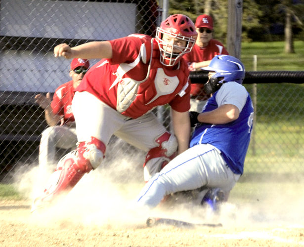 Tribune Chronicle / Bob Ettinger Badger catcher Koby Wear looks for the next play after attempting to tag Maplewood's Hunter Bates on a play at the plate at Mecca Community Park on Monday. Bates was safe on the play.