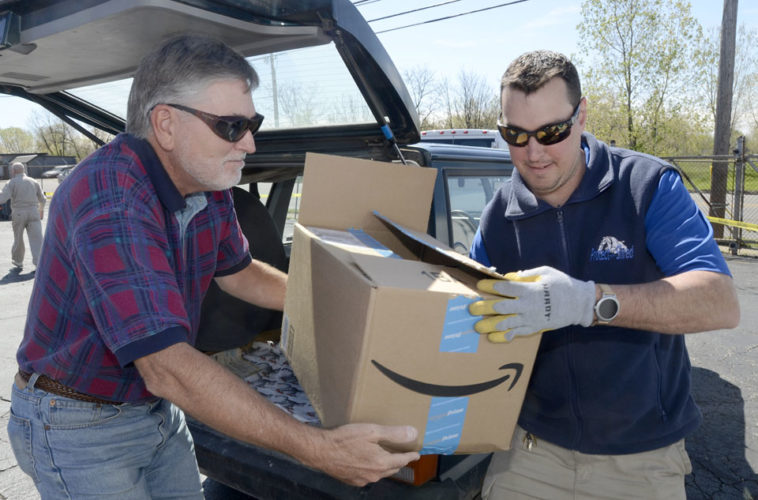 042417...R RECYCLE 3...Warren...04-24-17...Mark Bumstead of Cortland, left, hands over a box of paperwork to Jeffrey Muresan from Protect-n-Shred of Cortland to be shredded during the Tribune Chronicle's Earth Day event...by R. Michael Semple