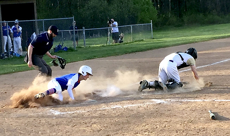 Tribune Chronicle / Joe Simon Western Reserve's Ryan Demsky, left, slides in safely before Champion catcher Nolan Yartz  can apply the tag as the home plate umpire looks on Wednesday in Champion.