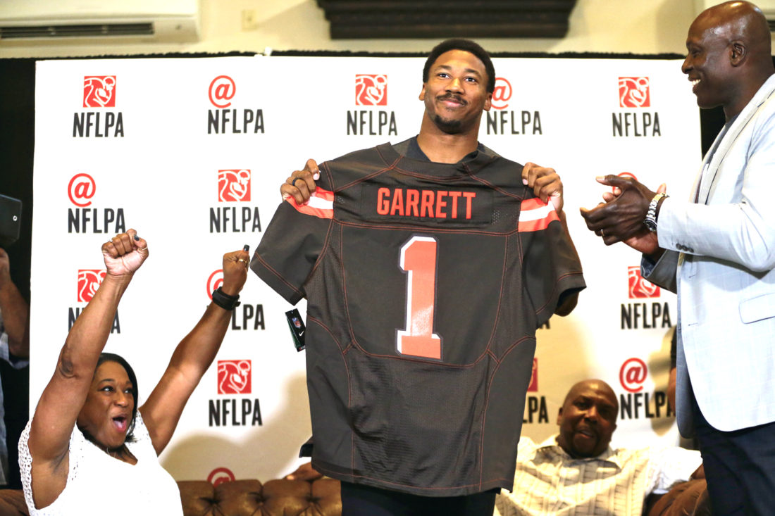 AP  Texas A&M's Myles Garrett holds up a Cleveland Browns jersey at the Terre Verde Golf Course in Arlington, Texas, Thursday as his mother, Audrey Garrett, left, cheers with Bruce Smith, right, after Garrett was taken as the No. 1 pick in the NFL football draft.