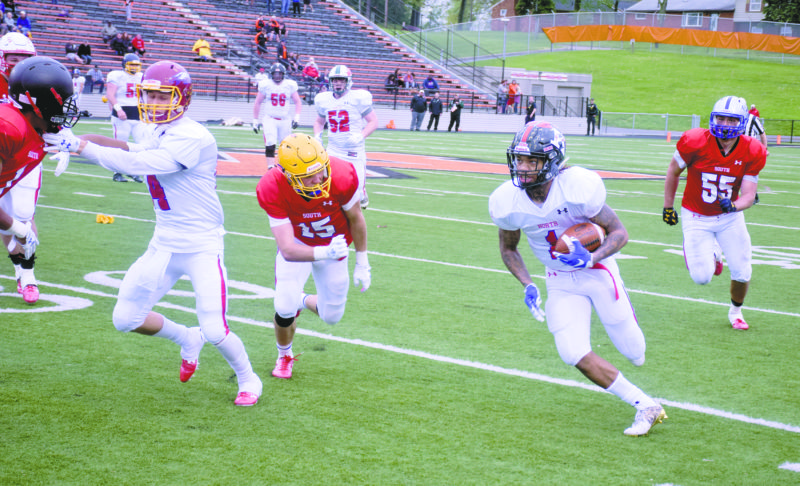 Tribune Chronicle / JohnVargo Warren G. Harding's Lynn Bowden turns upfield as St. Mary's Julius Fisher pursues Saturday in the Ohio High School Football Coaches Association Division I-III North-South All-Star football game at Massillon.