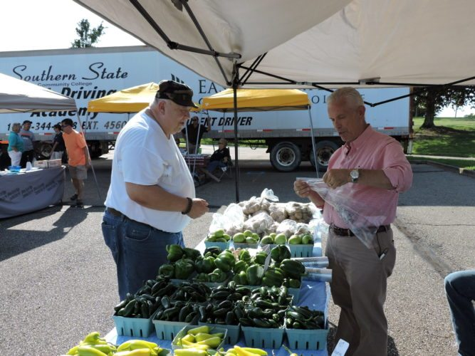 "FRIED GREEN TOMATOES —  Frank Shelton of Steubenville, left, waited to buy a green tomato from U.S. Rep. Bill Johnson, R-Marietta, Wednesday afternoon at the Farmers' Gateway Market. Shelton said he was in the mood for a fried green tomato for dinner and Johnson was conducting his ""undercover congressman"" role at the market. -- Dave Gossett"