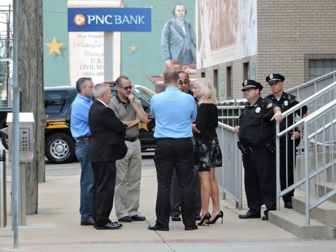 A SOMBER SIDEWALK CONFERENCE — Jefferson County commissioners, from left, Thomas Graham, David Maple and Tom Gentile listened while assistant Prosecutor Jeff Bruzzese, Sheriff Fred Abdalla and Prosecutor Jane Hanlin discussed the apparent suicide of convicted felon Jason Binkiewicz Friday morning in the Jefferson County Courthouse. Standing guard at the side entrance to the courthouse were City Police patrolmen Shawn Scott and Eric Hart. -- Dave Gossett