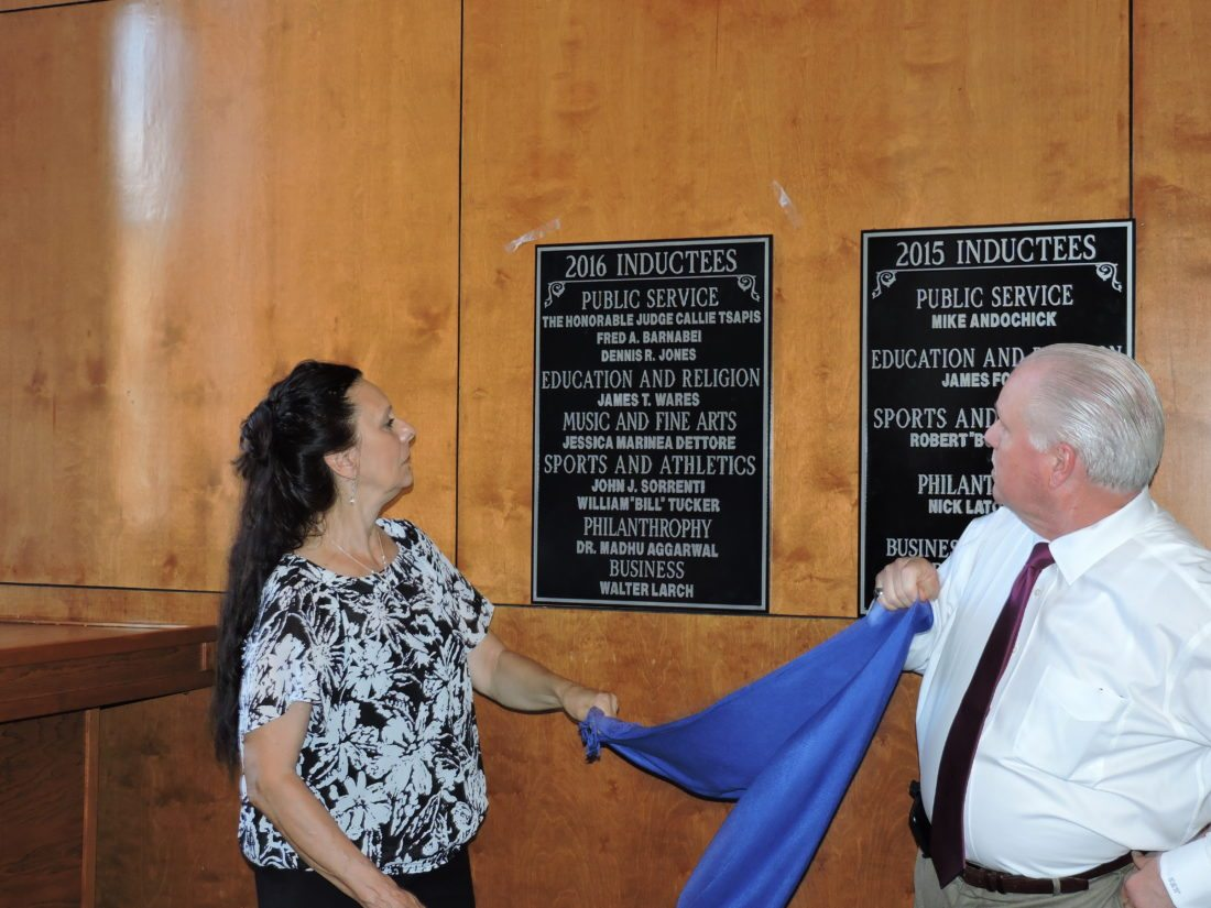 UNVEILING — Weirton Hall of Fame Committee members Linda Krynicki and Chuck Wright unveil the plaque listing the names of those inducted as part of the hall's 2016 class. The plaque is on display in the Weirton Room of the Millsop Community Center. -- Craig Howell